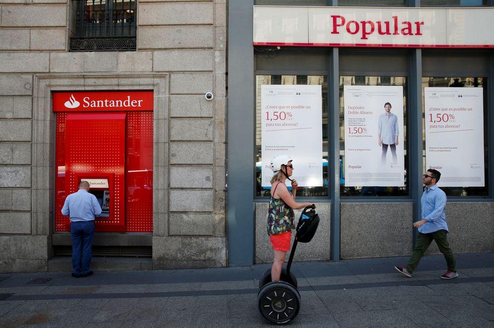 Foto: Un hombre utiliza un cajero del Santander junto a una sucursal del Banco Popular. (Reuters)