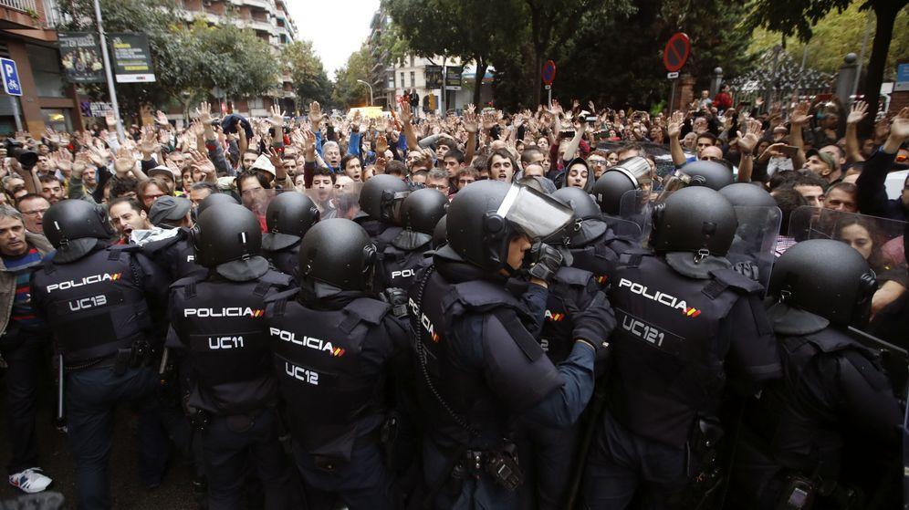 Foto: Agentes antidisturbios de la Policía Nacional forman un cordón de seguridad en los alrededores del colegio Ramón Llull de Barcelona el 1-O. (EFE)