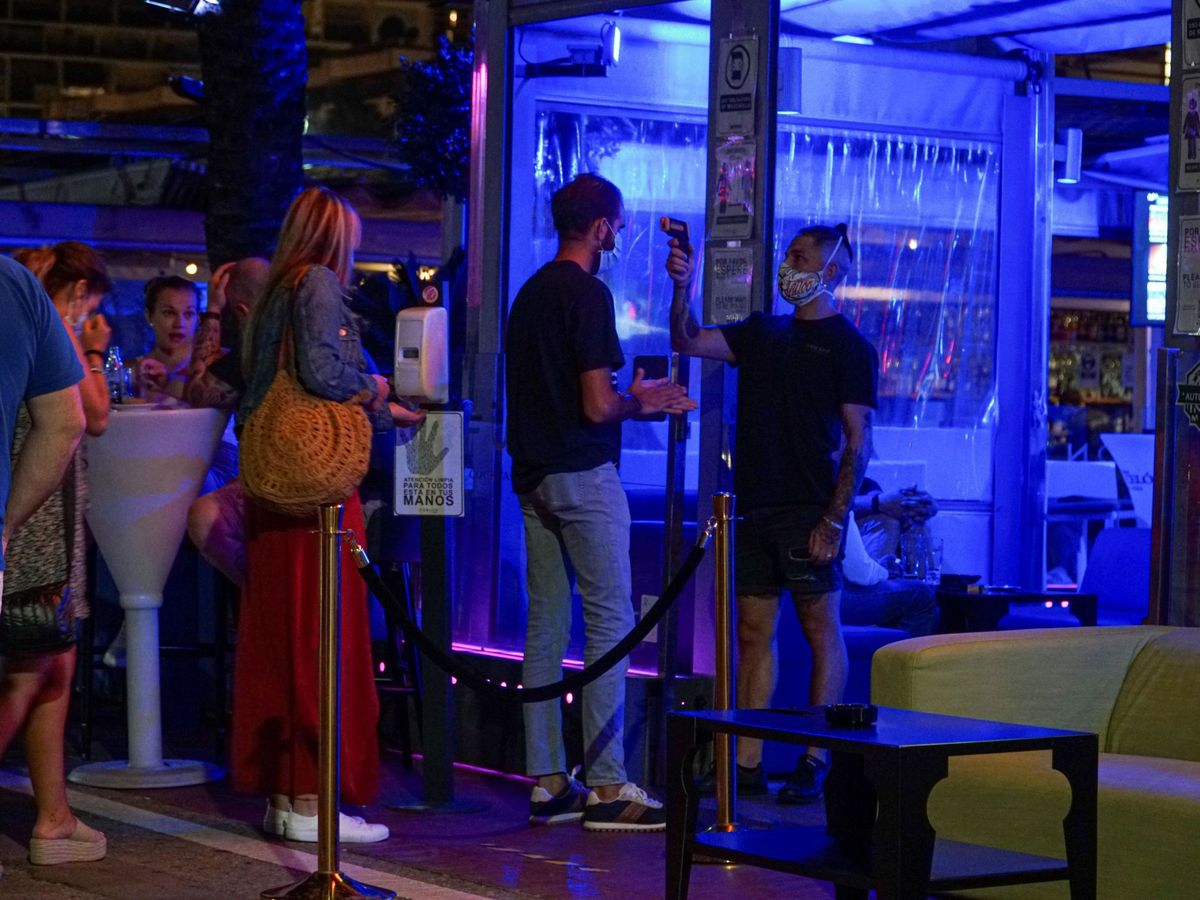 Foto: Un empleado toma la temperatura a un joven en un 'pub'. (EFE)