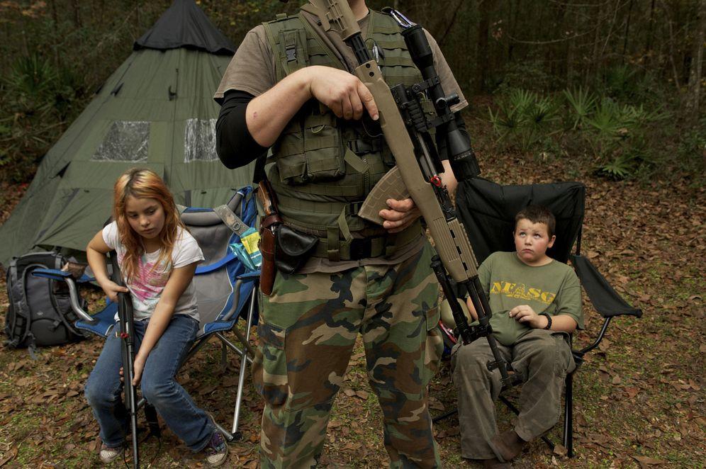 Foto: Un miembro del Grupo de Supervivencia de Florida Norte espera con su rifle delante de sus hijos antes de un ejercicio paramilitar, en febrero de 2013. (Reuters)
