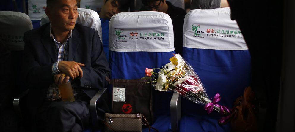 Foto: Un hombre se sienta junto a las cenizas de un familiar mientras viaja en un ferri hacia un entierro en el mar, en Shanghai, China (Reuters).