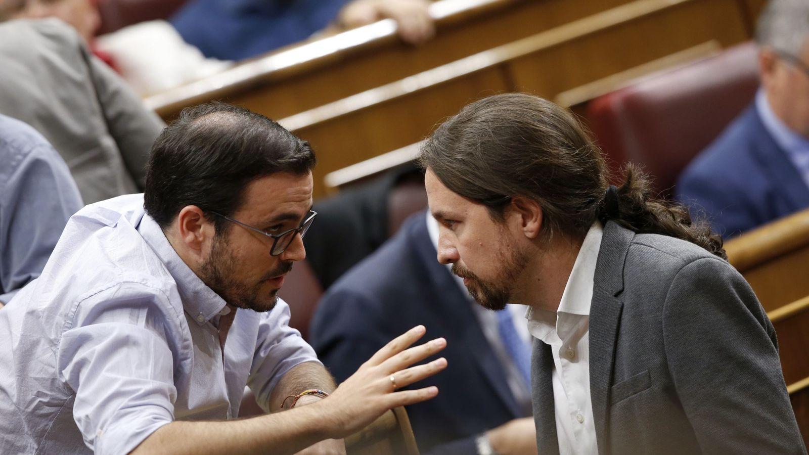 Foto: El secretario general de Podemos, Pablo Iglesias (d), conversa con el coordinador general de IU, Alberto Garzón (i), al inicio de un pleno del Congreso. (EFE)