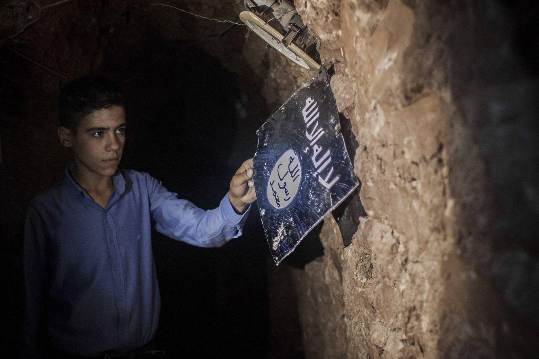 Foto: El hijo de Hanim muestra una placa metálica del ISIS en un túnel subterráneo bajo su casa.  (Foto: Ethel Bonet).