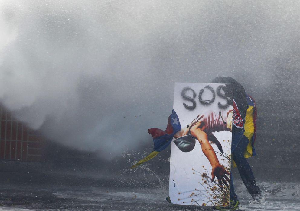Foto: Un manifestante antichavista se cubre tras un escudo decorado durante una protesta el jueves en Caracas (Reuters).