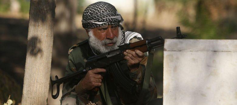 Un combatiente de una brigada que lucha junto al Ejército de Liberación Sirio se pone a cubierto en Alepo (Reuters).