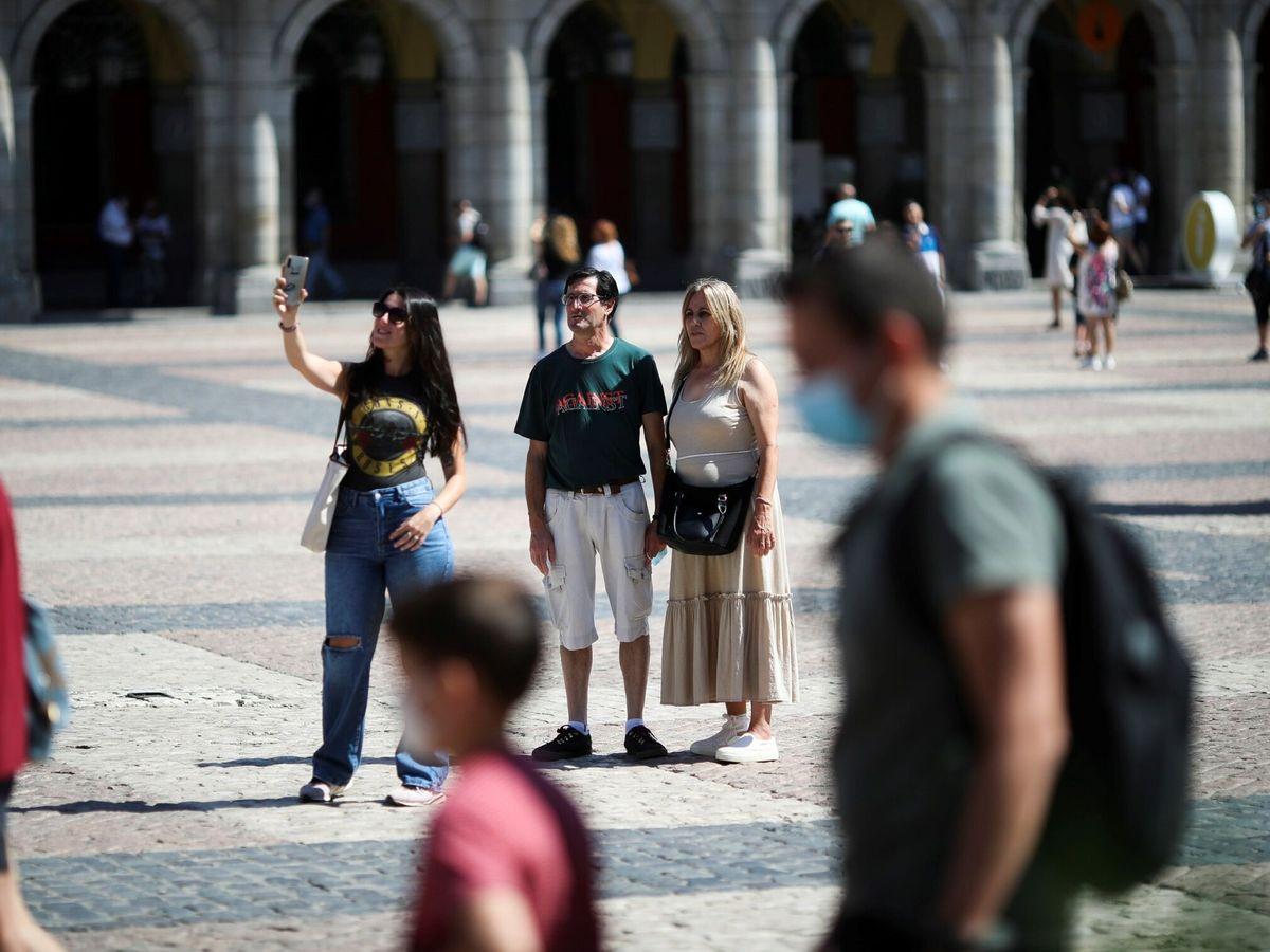 Foto: Varias personas pasean con y sin mascarilla, en la Plaza Mayor de Madrid. (EFE)