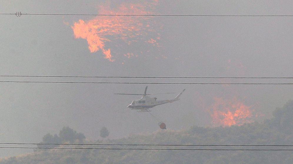 Foto: Un helicóptero trabaja en el incendio forestal en el barranco de Beneixama. (EFE)