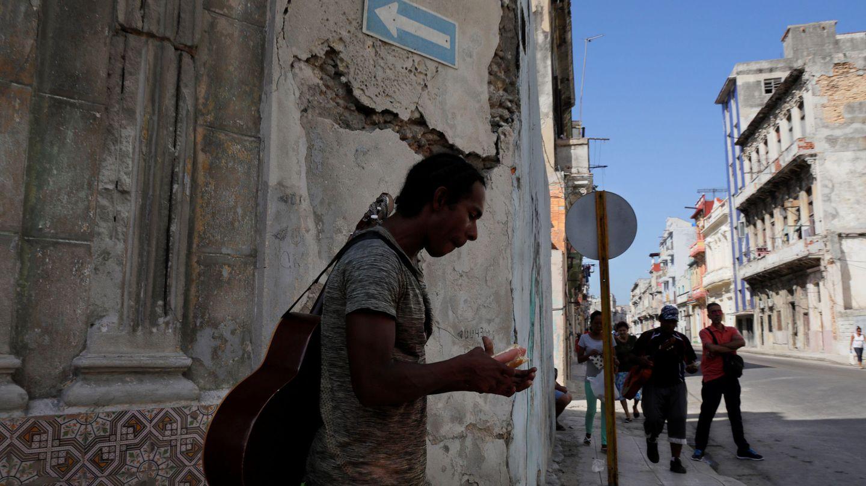 Un músico se come un perrito caliente en una calle de La Habana, en agosto de 2018. (Reuters)