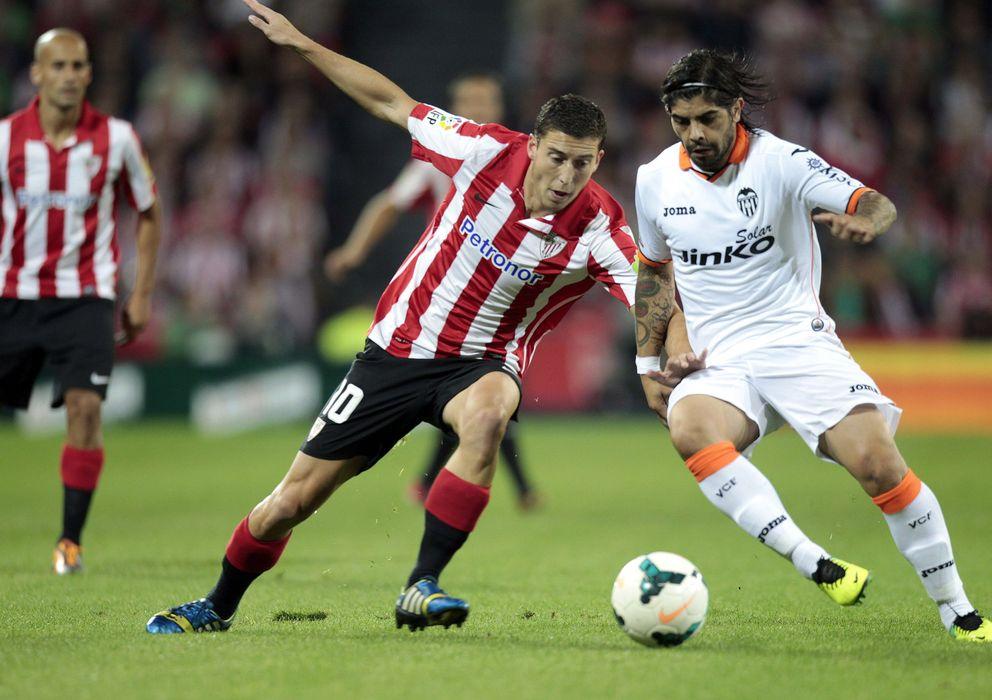 Foto: Banega controla el balón ante la presión de De Marcos, en el Athletic-Valencia de la temporada pasada. (EFE)