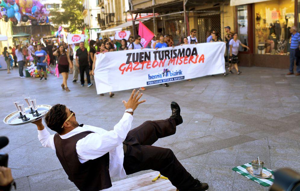 Foto: Las juventudes de Sortu se manifiestan contra el turismo en San Sebastián esta pasada Semana Grande junto a un artista callejero. (Reuters)
