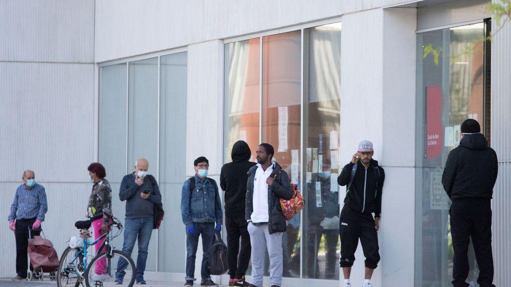 Foto: Varias personas esperan a que el centro de Casa Llacuna en Poblenou, Barcelona, reparta raciones de comida (EFE)