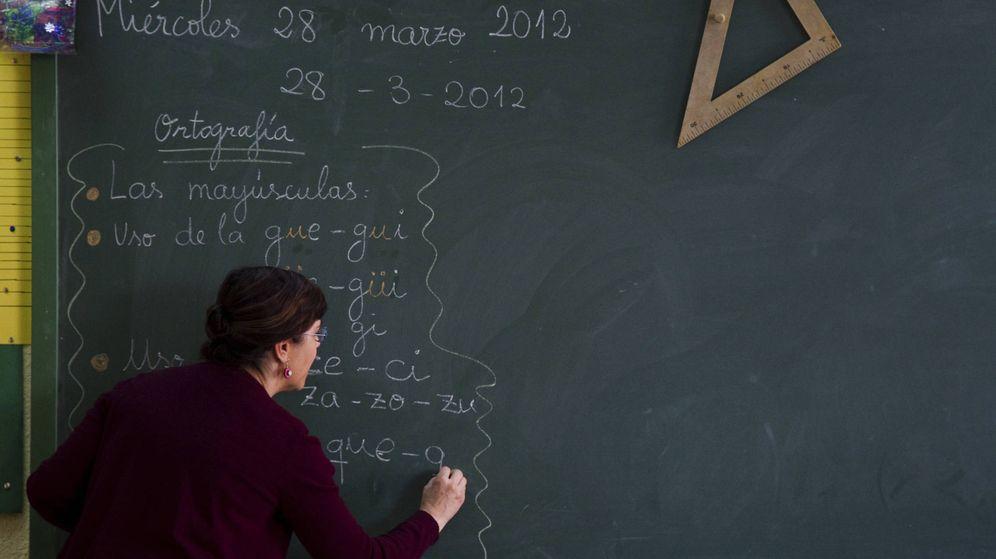 Foto: Una profesora escribe en la pizarra en un colegio público de Madrid. (Reuters)