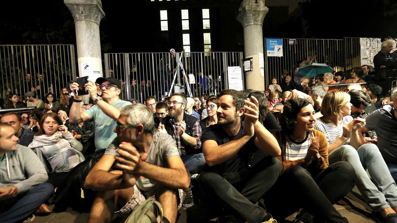 Varias personas se reúnen frente a las puertas de un colegio para no dejar entrar a la Guardia Civil. (EFE)
