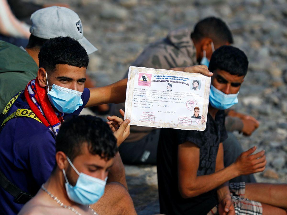 Foto: Un joven de origen magrebí muestra su certificado de estudios tras su llegada en patera. (Reuters)