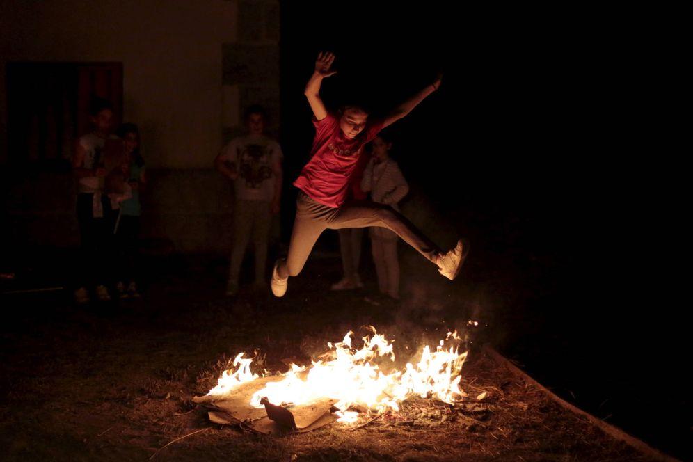 Foto: Una niña salta la hoguera en la noche de San Juan.
