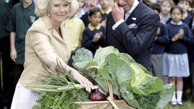 Camilla Parker y el príncipe Carlos de Inglaterra, tras recibir una cesta llena de verduras durante un encuentro con jardineros voluntarios en el parque de St. James. (EFE)