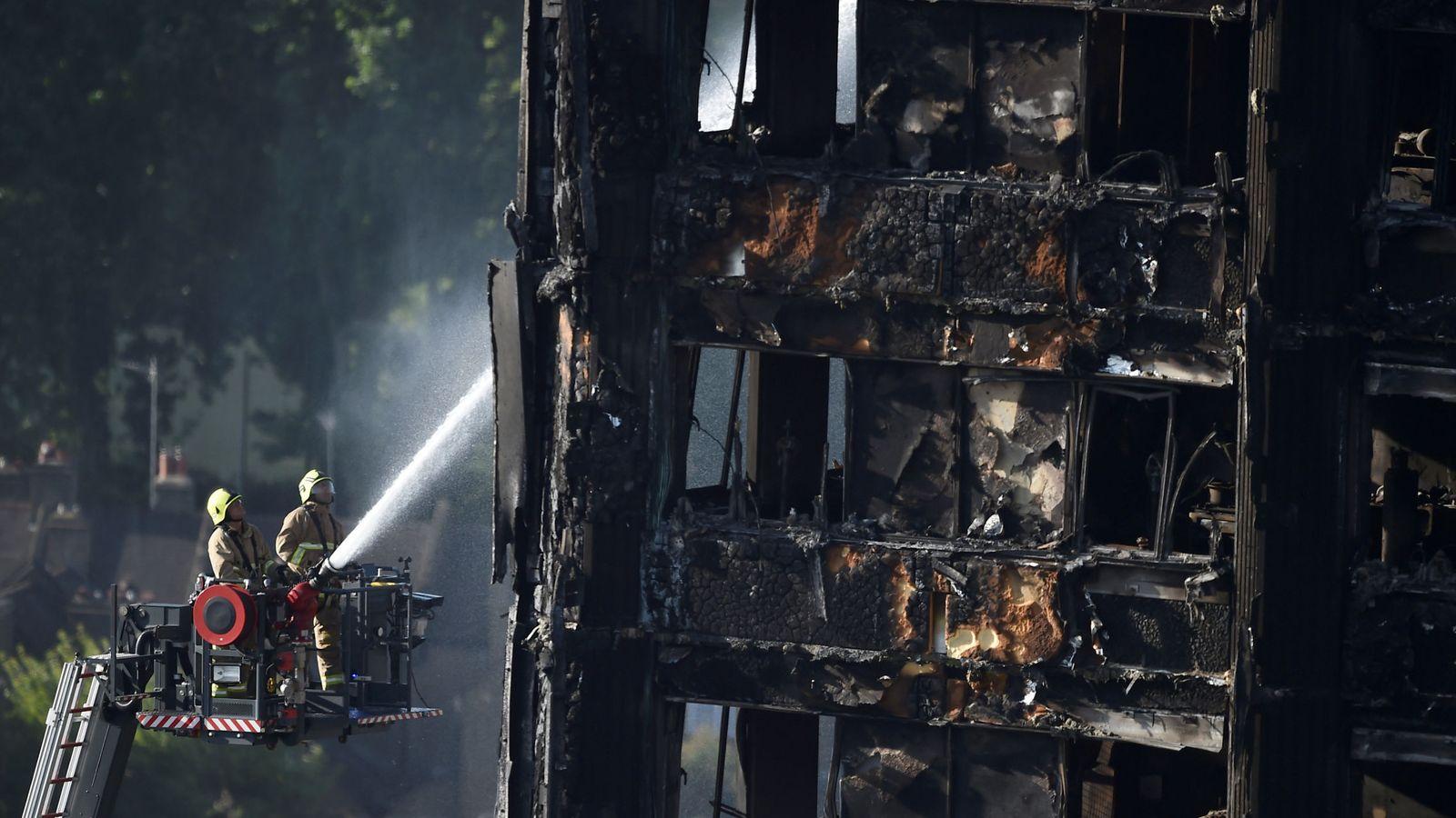 Foto: Dos bomberos echan agua en la fachada de la torre Grenfell, en Londres. (Reuters)