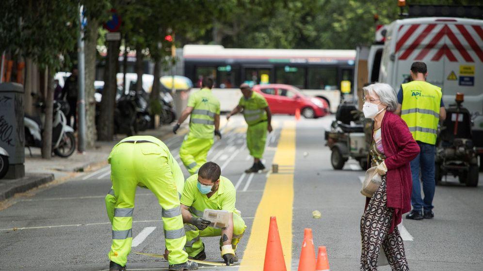 Foto: Operarios del Ayuntamiento de Barcelona trabajan contrarreloj en la ampliación de 12 kilómetros de aceras y de la red de itinerarios ciclables para la desescalada. (EFE)