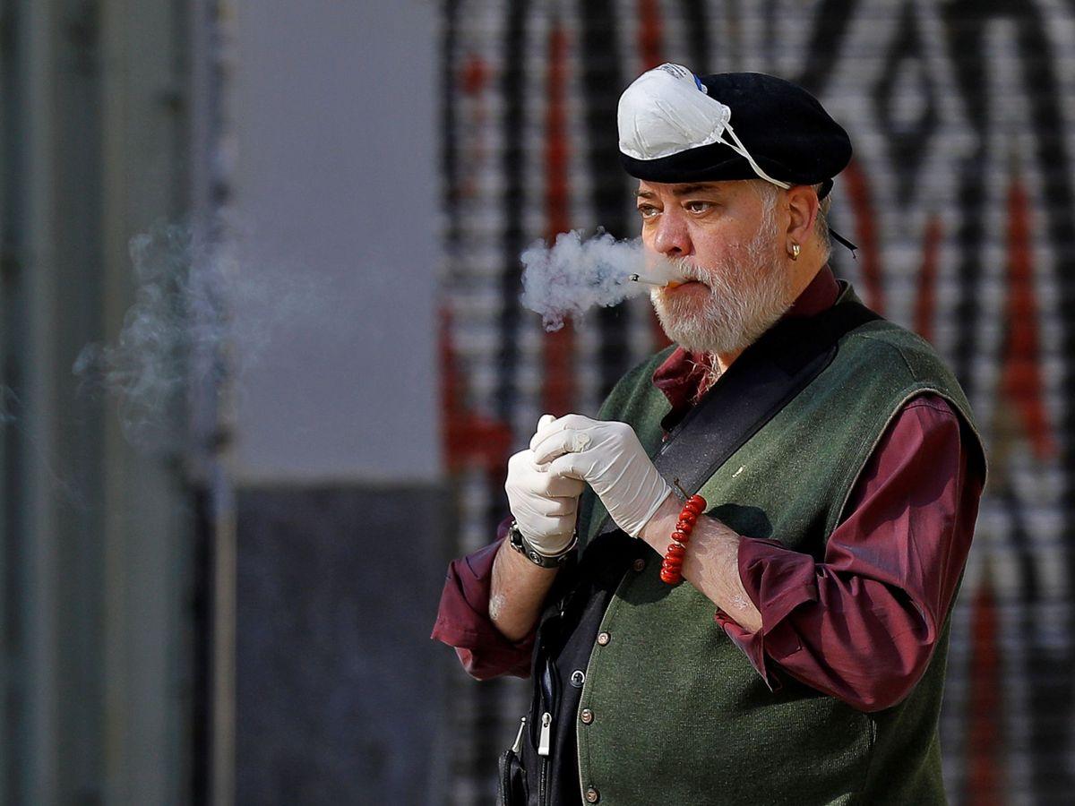 Foto: Un hombre se retira por un momento su mascarilla de protección para fumar. Foto: EFE Manuel Bruque