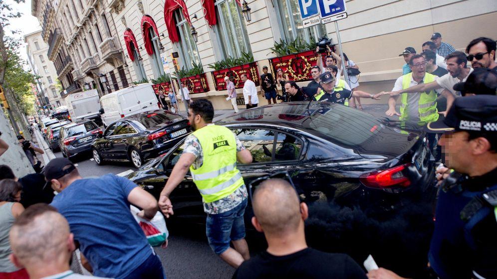 Foto: Taxistas increpan a un coche frante al hotel Palace durante la manifestación por las calles de Barcelona con motivo de la huelga. (EFE)