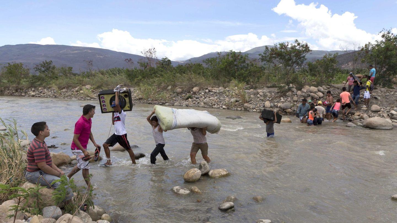 Un grupo de colombianos transporta objetos sobre el río Táchira, en agosto de 2015. (Reuters)