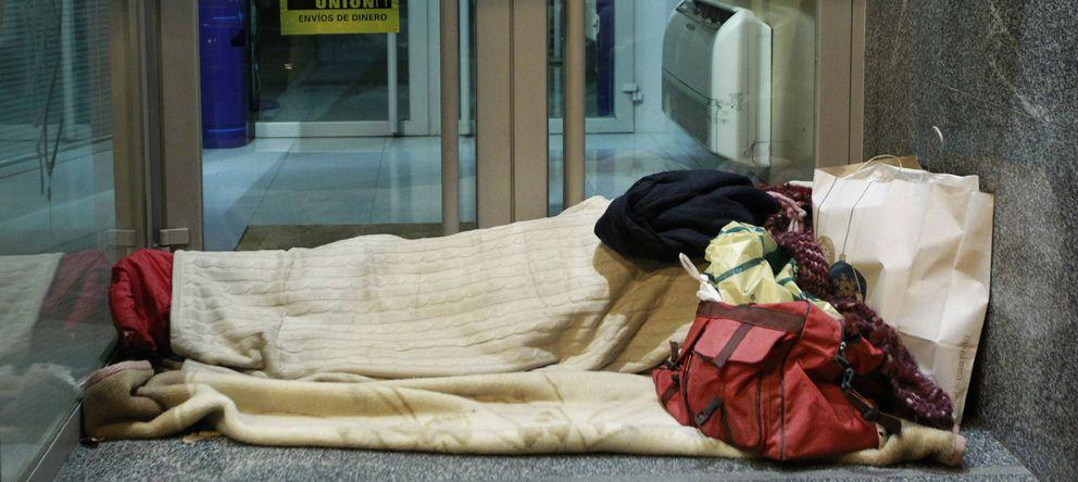 Foto: Un indigente se dispone a pasar la noche a las puertas de una entidad bancaria. (EFE)