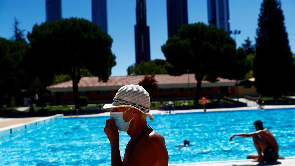 Foto: Una persona con mascarilla en una piscina de Madrid. (EFE)