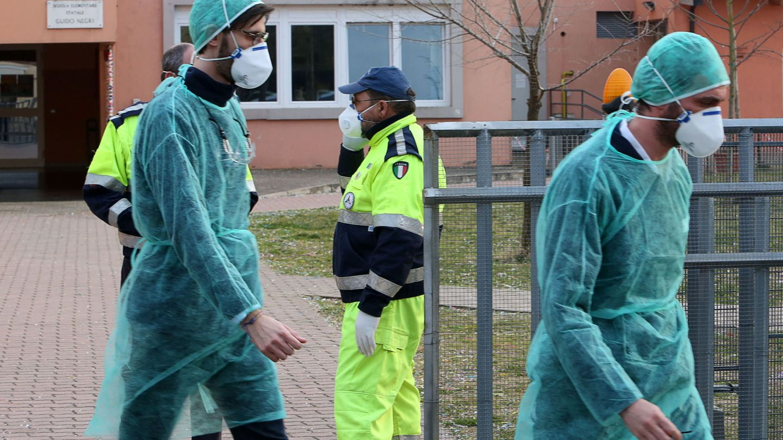 Las personas usan mascarillas protectoras frente a una escuela primaria cerrada en Vo 'Euganeo, Padua. (EFE)