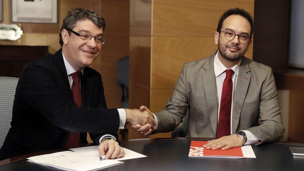 Foto: El ministro de Energía, Álvaro Nadal, estrecha la mano al portavoz socialista en el Congreso, Antonio Hernando, este 21 de diciembre. (EFE)