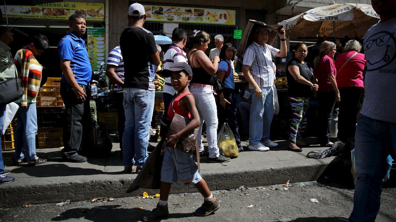 Foto: Alexandre, de 7 años., vende bolsas de plástico en una cola ante una pollería de Caracas, el 8 de diciembre de 2015 (Reuters).