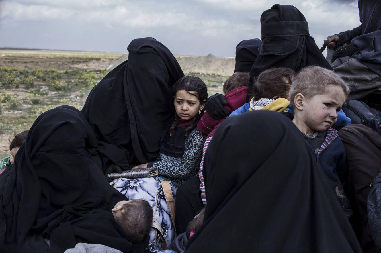 Foto: Mujeres con sus hijos llegan al campo de desplazados huyendo de los combates en Baghuz, último bastión del Estado Islámico en Siria. (J.M. López)