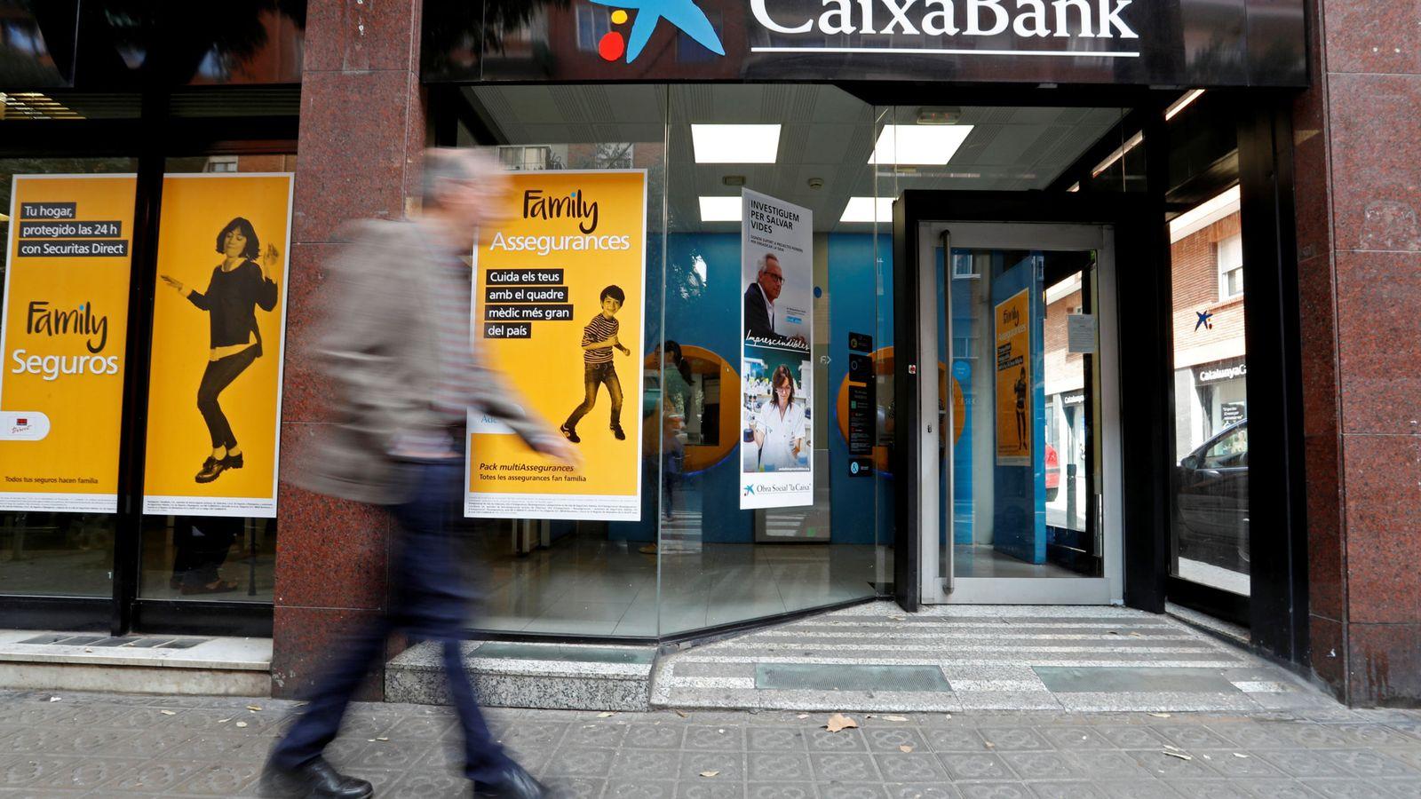 Foto: Un hombre pasa frente a una oficina de CaixaBank. (Reuters)