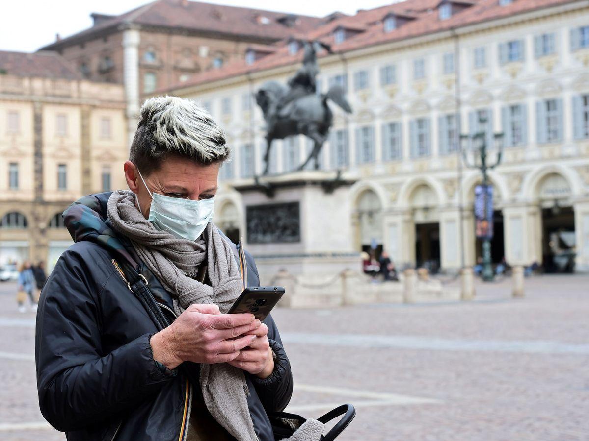 Foto: Una mujer con mascarilla protectora mira su móvil en una plaza de Turín, Italia (REUTERS)