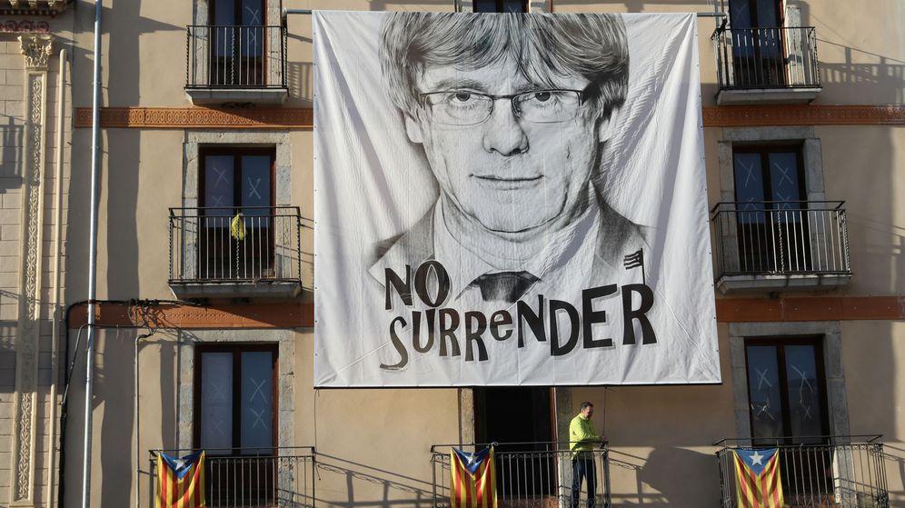 Foto: Un hombre coloca una pancarta del expresidente de la Generalitat de Cataluña Carles Puigdemont en Barcelona. (Reuters)