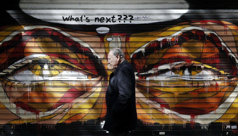 Foto: Un griego pasa ante una pintada en Atenas, el pasado 25 de febrero. (Reuters)