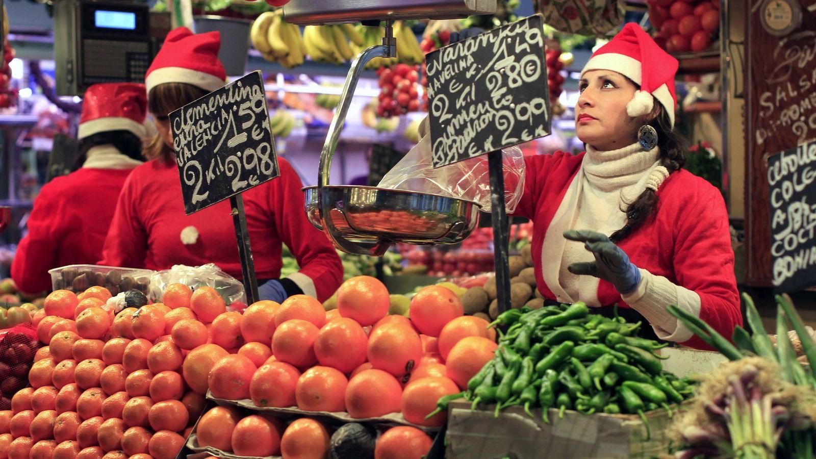 Foto: Compras en una frutería del Mercado de la Boquería de Barcelona para la cena de Nochebuena. (EFE)