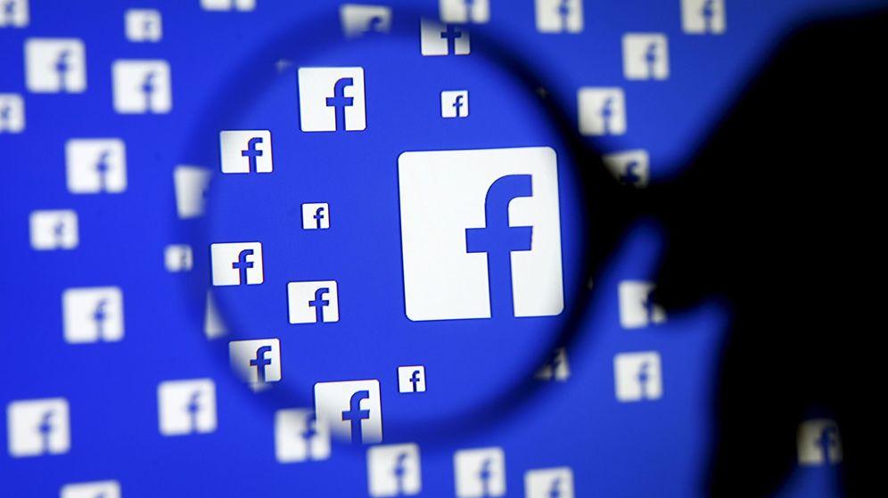 Foto: Un hombre posa una lupa sobre el logo de Facebook. (Reuters)