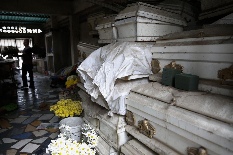 Foto: Un trabajador prepara flores junto a unos ataúdes en una funeraria de Caracas (Reuters).