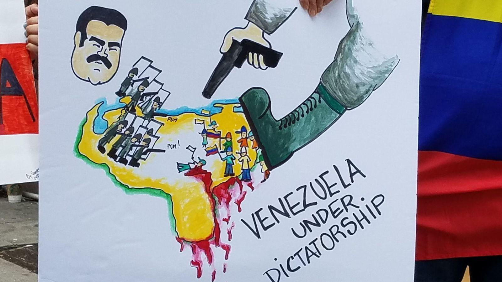 Foto: Una persona sostiene un cartel durante una manifestación de venezolanos frente al consulado de su país en Nueva York. (EFE)