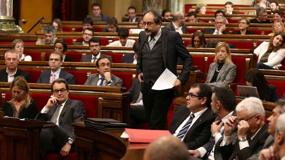 Foto: Artur Mas sentado, ve pasar al líder de la CUP Antonio Baños en el segundo debate de investidura. (EFE)