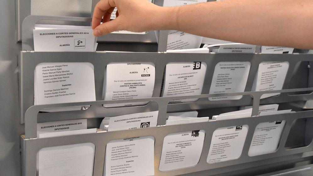 Foto: Una persona elige su papeleta en una cabina en un colegio electoral de Almería. (Efe)
