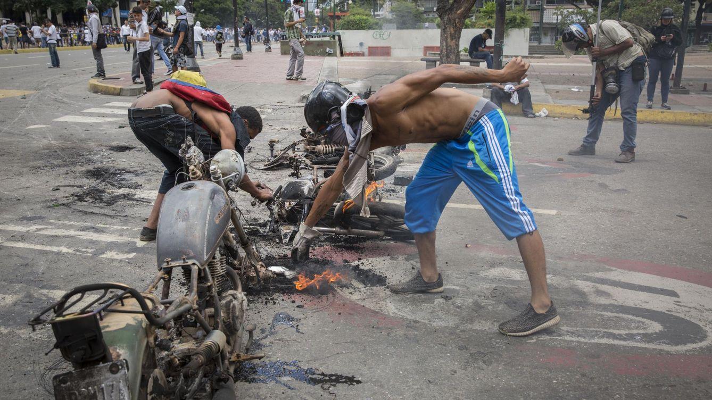 Foto: Manifestantes opositores reconstruyen unas barricadas con motocicletas quemadas en Caracas, ayer, 30 de julio de 2017. (Reuters)