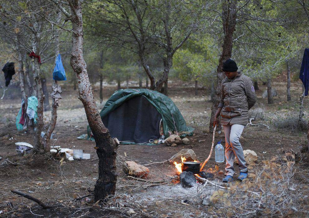 Foto: Marie, de Camerún, aviva un fuego en el campamento clandestino de Bolingo, frente a Melilla (Reuters).