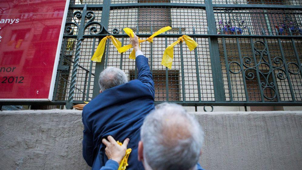 Foto: Dos de los miembros de los grupos de defensa y resistencia (GDR) —contrarios a la independencia de Cataluña— retiran los lazos amarillos previamente colocados por CDR. (EFE)
