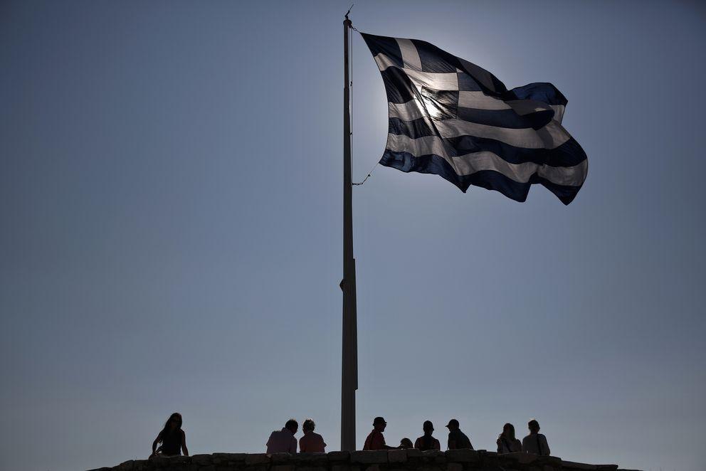 Foto: Un grupo de turistas bajo la bandera griega en lo alto de la colina de la Acrópolis, en Atenas, en julio de 2013 (Reuters).