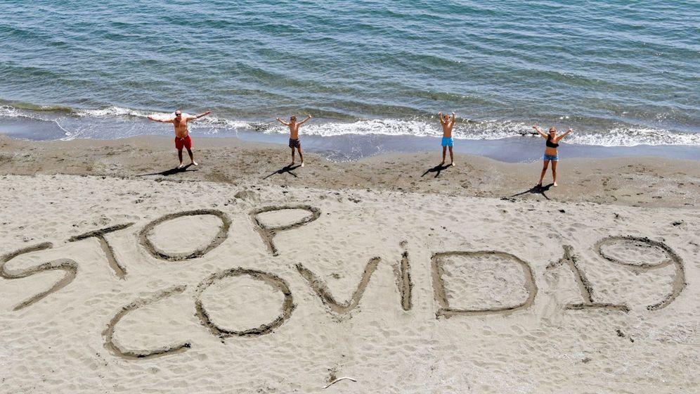 Foto: Una familia escribe la frase Stop covid-19 en la arena de una playa de Nápoles, Italia. (EFE)