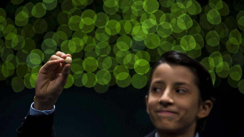 Foto: Un niño de San Ildefonso sostiene una bola durante la lotería de Navidad. (EFE)