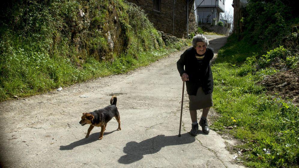 Foto: Una mujer pasea por una aldea ourensana donde ella es la única vecina estable. (EFE)