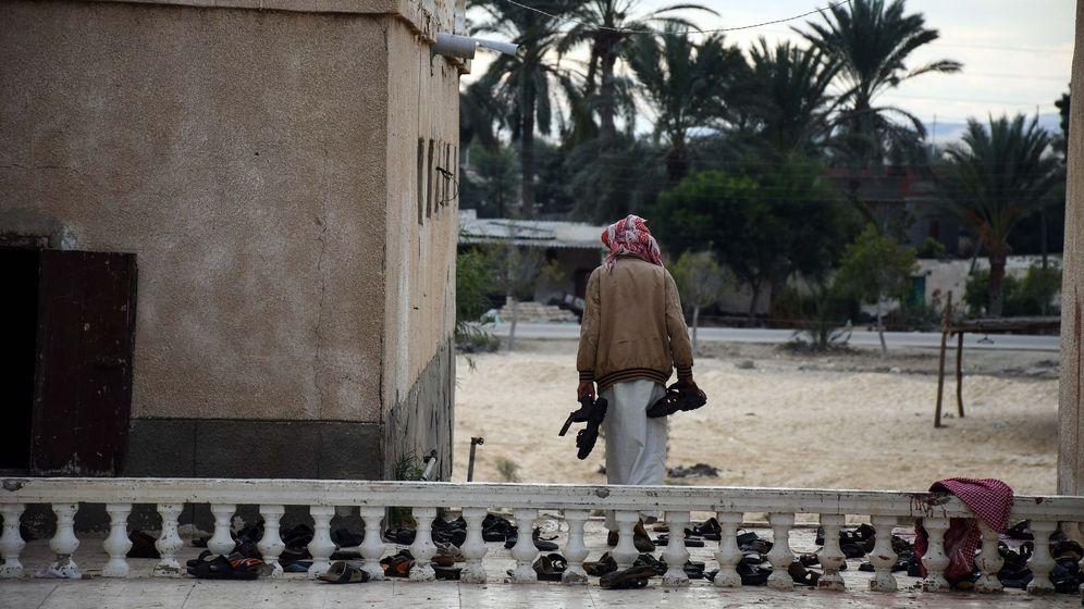 Foto: Un hombre recoge los objetos pertenecientes a las víctimas del atentado de la mezquita Al Rawda, el 25 de noviembre de 2017. (EFE)