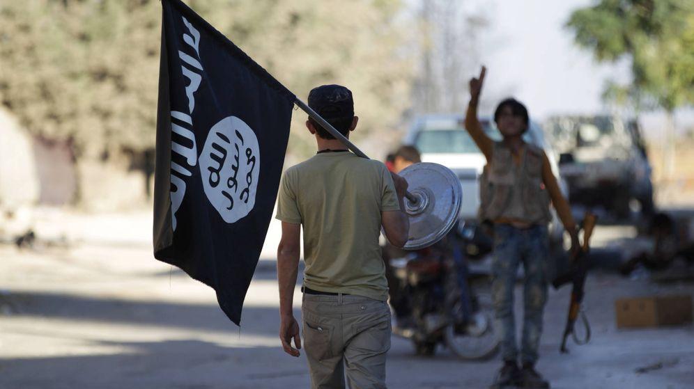 Foto: Un rebelde quita una bandera que pertenecía al Estado Islámico. (Reuters)
